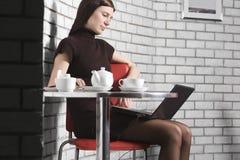 使用膝上型计算机的妇女在咖啡馆 免版税库存照片