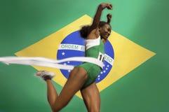 Σπάσιμο δρομέων μέσω της ταινίας γραμμών λήξης πέρα από τη βραζιλιάνα σημαία Στοκ Φωτογραφία