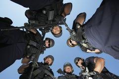 有站立反对天空的枪的警察 库存图片