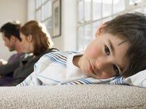放松在有父母的沙发的男孩在背景中 免版税图库摄影
