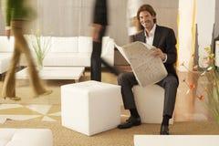 拿着报纸的商人,当走在办公室时的工友 免版税库存照片