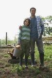 父亲和儿子有猪的在猪圈 免版税库存图片