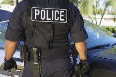站立反对汽车的制服的警察 免版税库存图片