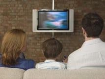 在沙发的家庭观看的电视 免版税库存照片