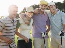 高尔夫球场的快乐的高尔夫球运动员 免版税库存照片