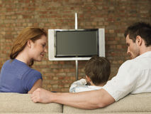 看男孩的父母在家看电视 免版税库存照片