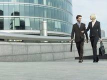 走在办公楼之外的商人 免版税库存照片