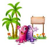 在棕榈树附近的两个妖怪 免版税库存照片