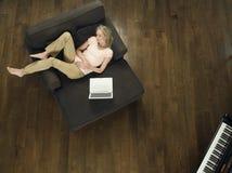 有膝上型计算机的睡觉在沙发的妇女顶视图  库存图片
