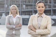 站立胳膊的确信的年轻女实业家画象横渡户外 免版税库存图片
