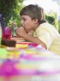 吃杯形蛋糕的年轻男孩在生日聚会 免版税库存照片