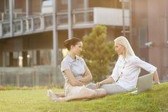 看彼此的年轻确信的女实业家在办公室草坪 免版税图库摄影