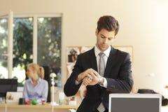 看他的手表的英俊的商人 免版税库存图片