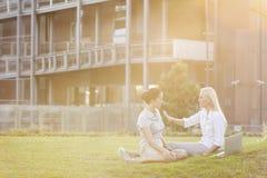年轻女实业家谈论在办公室草坪 免版税库存图片