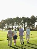 走在高尔夫球场的高尔夫球运动员 免版税图库摄影