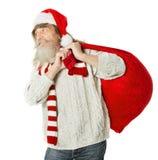 有胡子的圣诞节老人在运载圣诞老人袋子的红色帽子 免版税图库摄影