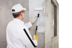 与一个漆滚筒的工作者飞沫在水泥墙壁上 库存图片