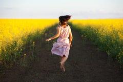 愉快的妇女跳到天空在黄色草甸在日落 库存图片