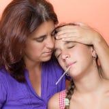采取温度她病的女儿的担心的母亲 免版税库存照片