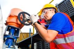 工作在工厂或公共事业的阀门的技术员 免版税库存图片