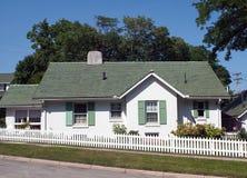 与白色尖桩篱栅的绿色&白色村庄 免版税图库摄影