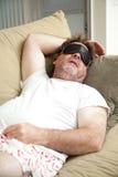 懒惰人睡着在长沙发 库存照片