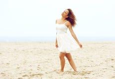 走在白色礼服的海滩的美丽的少妇 免版税库存照片