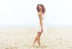 白色礼服的美丽的妇女走在沙子的在海滩 免版税图库摄影