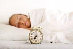 年轻睡觉的妇女和闹钟在床上 免版税库存图片
