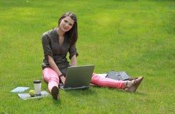 有一台膝上型计算机的妇女在草 免版税库存照片