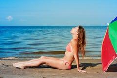 Красивая женщина загорая на пляже. Стоковые Фотографии RF
