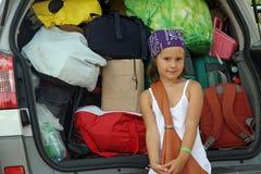 有袋子的美丽的微笑的在汽车的女孩和手提箱 免版税库存图片