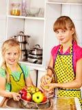 洗涤果子的孩子在厨房。 免版税库存图片