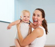 在家使用与逗人喜爱的微笑的婴孩的愉快的母亲 免版税库存照片