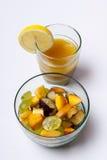 在白色背景和橙汁隔绝的水果沙拉。 免版税库存图片