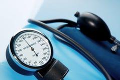 在蓝色背景的血压计 库存图片