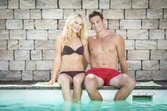 白肤金发的女孩和英俊的男孩游泳池的 免版税库存图片