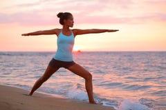 思考的瑜伽妇女在海滩的战士姿势 免版税库存照片