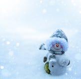 圣诞节雪人和蓝色雪背景 免版税库存图片