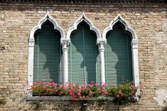 Роскошный цветистый балкон в венецианском стиле с сдобренными окнами Стоковая Фотография