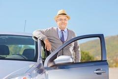 有摆在他的汽车旁边的帽子的微笑的成熟绅士外面 免版税库存图片