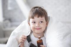 男孩饮用的咳嗽糖浆 库存图片
