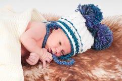 帽子的新出生的婴孩有大型机关炮的 免版税库存照片