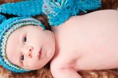 蓝色被编织的帽子的新出生的婴孩 库存图片