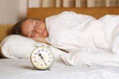 年轻睡觉的妇女和闹钟在床上 库存照片
