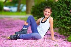 逗人喜爱的女孩四轮溜冰者在春天公园 库存照片
