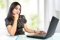 工作在她的办公室的繁忙的女商人 免版税库存图片