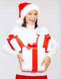 闪光圣诞老人帽子的妇女有许多礼物盒的 免版税库存图片