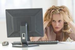 看台式计算机的沮丧的女实业家在办公室 图库摄影