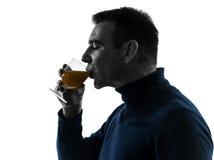 喝橙汁剪影画象的人 免版税库存图片